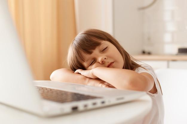 Foto interna da menina pré-escolar com cabelo escuro, sentada na frente do computador laptop na cozinha e dormindo, adormecendo durante a chata aula online.