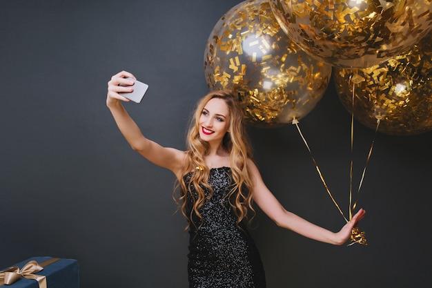 Foto interna da romântica aniversariante loira fazendo selfie. mulher caucasiana encaracolada sorridente, relaxando na festa com balões e presentes.