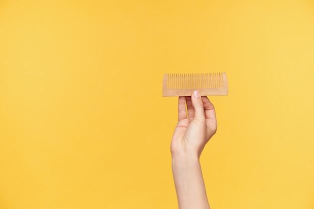 Foto interna das mãos de uma jovem mulher de pele clara com manicure nua segurando uma escova de cabelo de madeira horizontalmente enquanto é isolada sobre um fundo laranja