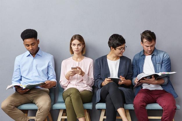 Foto interna de alunos inter-raciais sentados perto da sala de aula indo para passar no exame