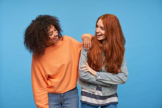 Foto interna de amigas positivas encantadoras rindo alegremente enquanto se olham, estando de bom humor enquanto ficam de pé sobre uma parede azul