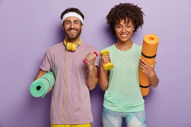 Foto interna de amigos homens e mulheres felizes e motivados treinando diariamente na academia, trabalhando no bíceps, levantando halteres