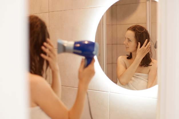Foto interna de atraente mulher de cabelos escuros secando o cabelo em frente ao espelho, sendo enrolada em uma toalha, olhando para si mesma, fazendo procedimentos matinais em casa.
