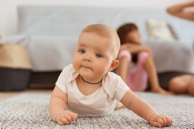 Foto interna de bebê fofo vestindo roupas brancas, deitado no chão, no tapete, em sua barriga, estudando o mundo ao redor por conta própria, olhando para a câmera com uma expressão curiosa.