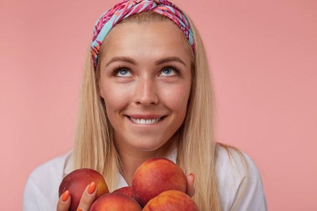 Foto interna de close-up de uma bela jovem com cabelo loiro, olhando pensativamente para cima e mordendo o lábio inferior posando