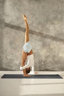 Foto interna de corpo inteiro de um homem musculoso e desportivo irreconhecível em roupas esportivas praticando ioga, fazendo pose de divisão em pé ou urdhva prasarita eka padasana, alongando isquiotibiais, panturrilhas e coxas