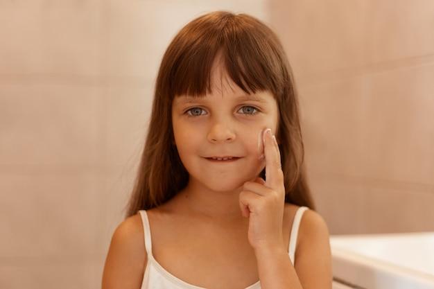 Foto interna de criança do sexo feminino com creme facial na bochecha, apontando o dedo no rosto, olhando diretamente para a câmera, vestindo camiseta branca sem mangas, fazendo procedimentos de beleza sozinho.