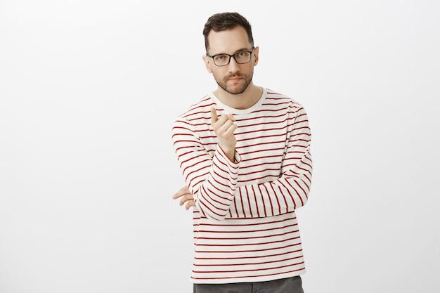 Foto interna de determinado empresário criativo de óculos escuros e camisa listrada, apontando com o dedo indicador e olhando sério, dando tarefa à equipe do escritório, de pé sobre a parede cinza