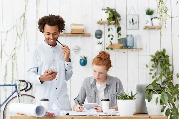 Foto interna de dois amigos trabalhando juntos em um projeto futuro