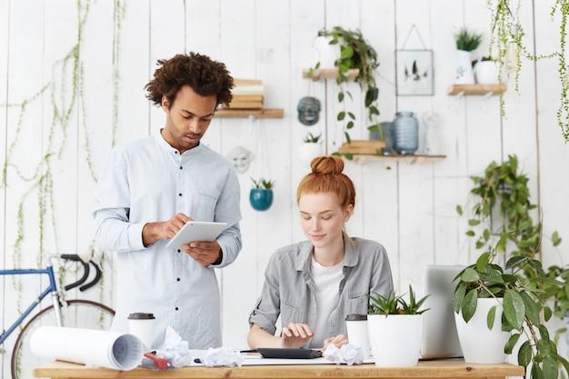 Foto interna de dois arquitetos trabalhando juntos em um projeto de construção comum