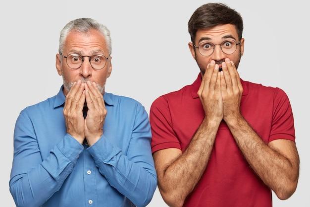 Foto interna de dois homens surpresos de diferentes idades cobrindo a boca com as duas mãos, olhando perplexos, recebendo notícias inesperadas, descobrindo sobre a quebra do negócio de sua família, isolado no branco