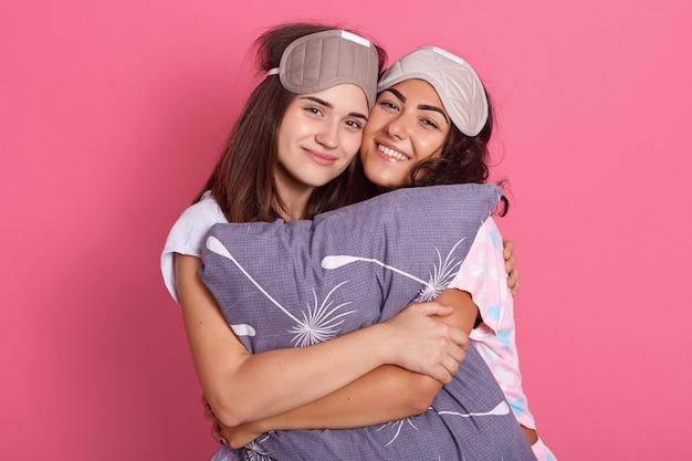 Foto interna de duas lindas garotas atraentes e felizes, sorrindo sinceramente enquanto olham para a câmera e se abraçam, usando máscaras de dormir e pijamas, abraçando o travesseiro contra a parede rosa.