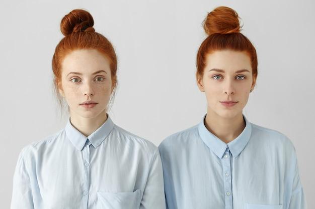 Foto interna de duas lindas garotas ruivas parecidas usando coques de cabelo iguais