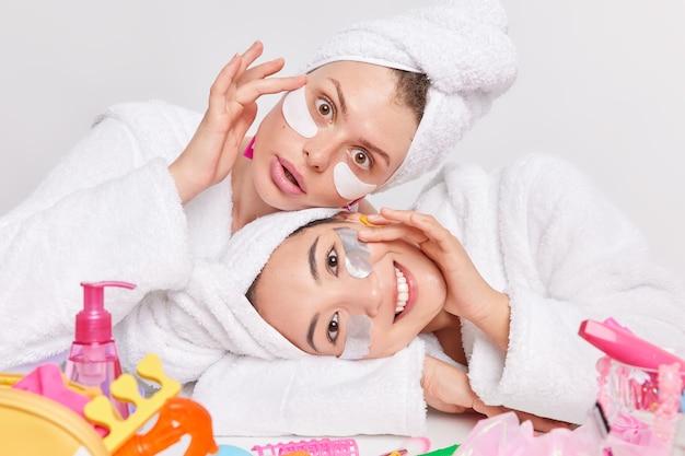 Foto interna de duas mulheres multiétnicas inclinando as cabeças aplicando adesivos de colágeno sob os olhos