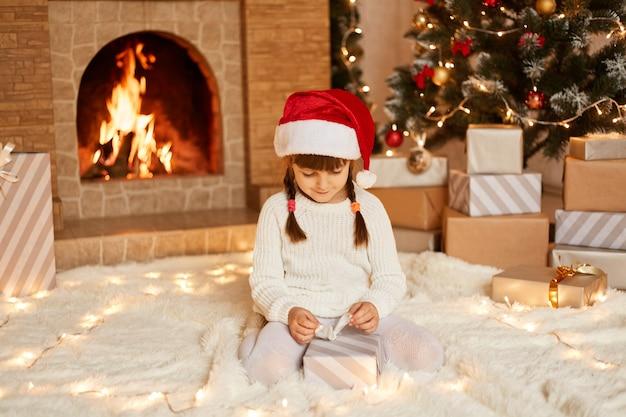 Foto interna de encantadora criança do sexo feminino com suéter branco e chapéu de papai noel, abrindo a caixa de presente do papai noel, posando na sala festiva com lareira e árvore de natal.