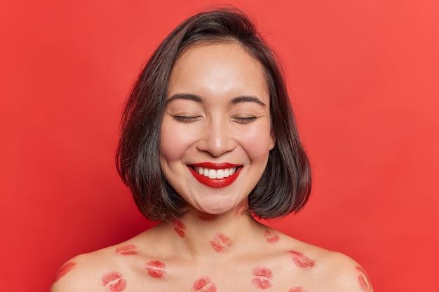 Foto interna de feliz senhora feminina com aparência oriental sorri com os dentes e mantém os olhos fechados usa batom vermelho posa sem camisa tem traços de lábios no corpo isolados sobre a vívida parede do estúdio