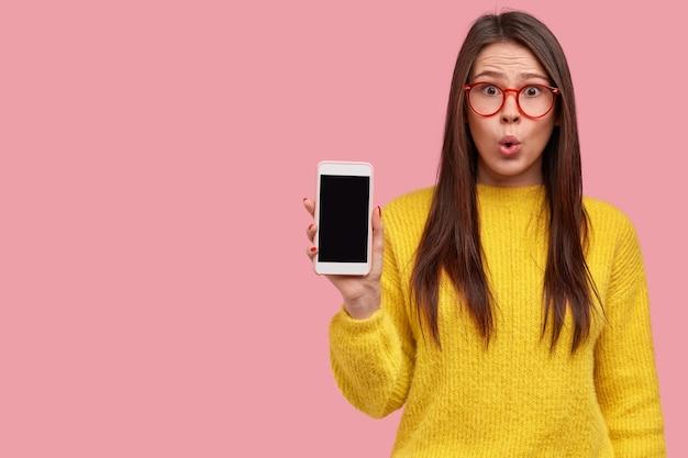Foto interna de hipster morena surpresa com expressão de espanto mostra celular com tela em branco, vê descontos em gadgets na loja, usa roupas amarelas