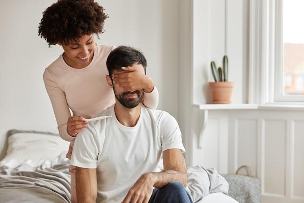Foto interna de jovem casal feliz com teste de gravidez posando em casa