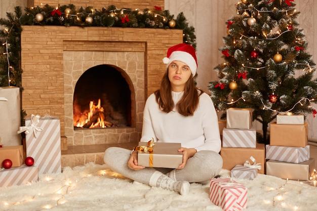 Foto interna de jovem ficar triste ou infeliz com o presente de natal, sentada no chão em um carpete macio e olhando para a câmera com lábios carnudos e expressão chateada, posando perto da lareira e da árvore de natal.