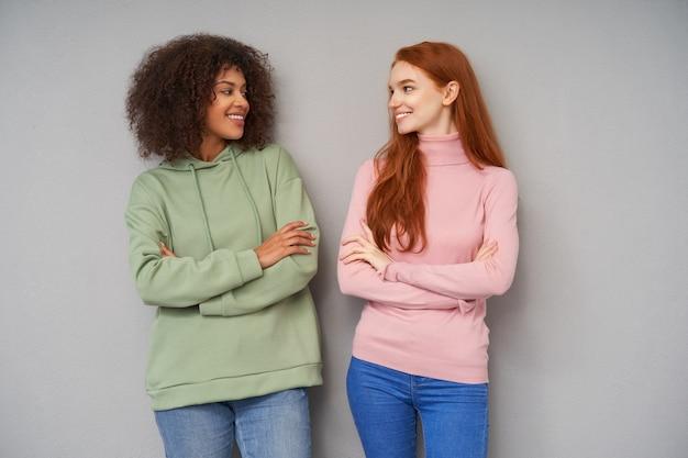 Foto interna de lindas mulheres jovens e alegres com penteado casual cruzando as mãos em pé sobre uma parede cinza, olhando positivamente uma para a outra e sorrindo agradavelmente