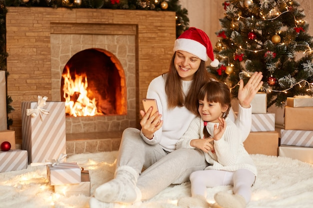 Foto interna de mãe e filha tendo videochamada ou transmissão ao vivo, acenando com as mãos para a câmera do telefone inteligente, posando perto da lareira e da árvore de natal.