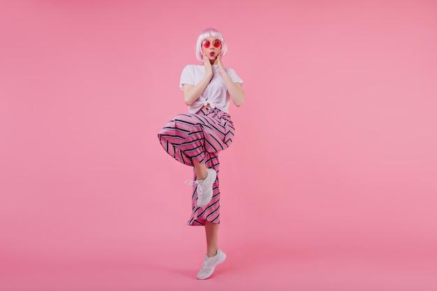 Foto interna de menina bonita espantada em peruca rosa engraçada posando na parede rosa. refinada senhora caucasiana em trajes da moda dançando e expressando emoções surpresas