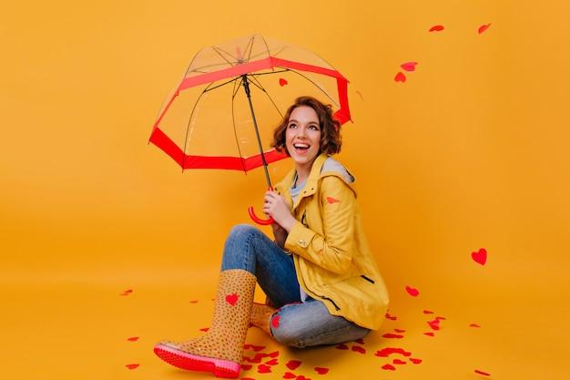 Foto interna de menina em sapatos de borracha da moda rindo sob o guarda-chuva. foto de estúdio de senhora em êxtase brincando no dia dos namorados.