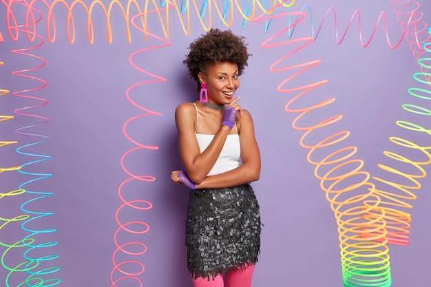 Foto interna de mulher alegre com penteado encaracolado