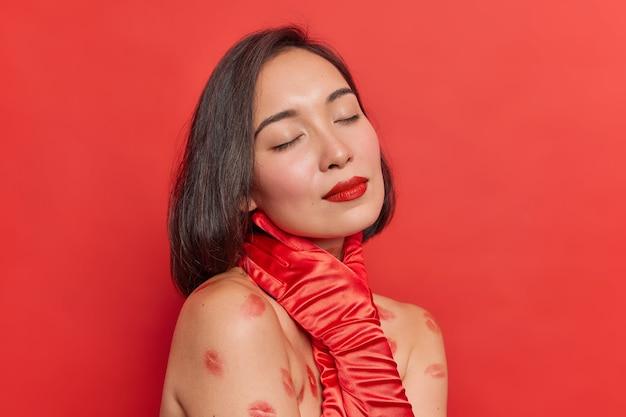 Foto interna de mulher asiática com maquiagem natural, batom vermelho, segurando a mão no pescoço, sem camisa, tem traços de batom no corpo isolados contra uma parede vívida