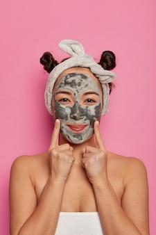 Foto interna de mulher bonita aplica máscara facial de limpeza com nutrientes, indica com os dedos da frente nas bochechas, se preocupa com a aparência, faz procedimentos de beleza em salão de spa, enrolada em toalha
