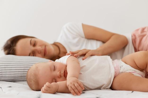 Foto interna de mulher dormindo e sua encantadora filha pequena deitada na cama com os olhos fechados, descansando à tarde, mamãe olhando para o bebê com muito amor e abraçando-a.