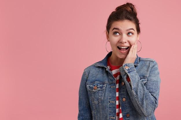 Foto interna de mulher feliz espantada e alegre com sardas, sorri e coloca a mão no rosto, vestindo uma camiseta listrada de jaqueta jeans, olhando para a esquerda para o copyspace; isolado sobre a parede rosa.