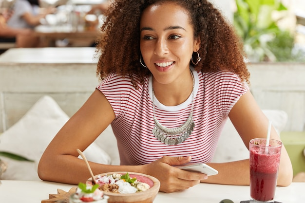Foto interna de mulher feliz tem bate-papos de cabelos cacheados online em redes sociais com amigos, usa um dispositivo eletrônico moderno e internet, senta-se em um café com uma bebida exótica e um prato. conceito de tecnologia