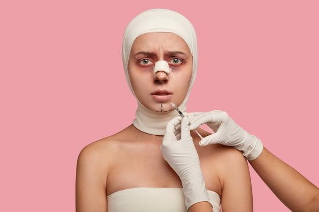 Foto interna de mulher jovem com expressão de descontentamento, procedimento de aumento dos lábios, recebe injeção de cirurgião irreconhecível