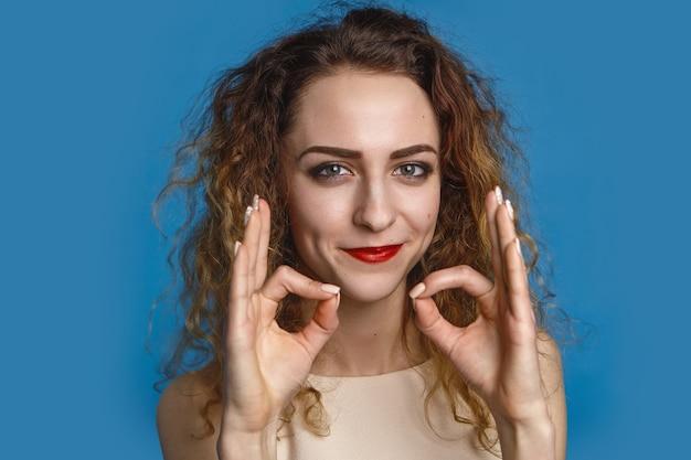 Foto interna de mulher jovem feliz em paz com cabelo encaracolado, sentindo-se relaxado, praticando ioga, meditação, sorrindo. consideração, tranquilidade, atmosfera calma, relaxamento e equilíbrio