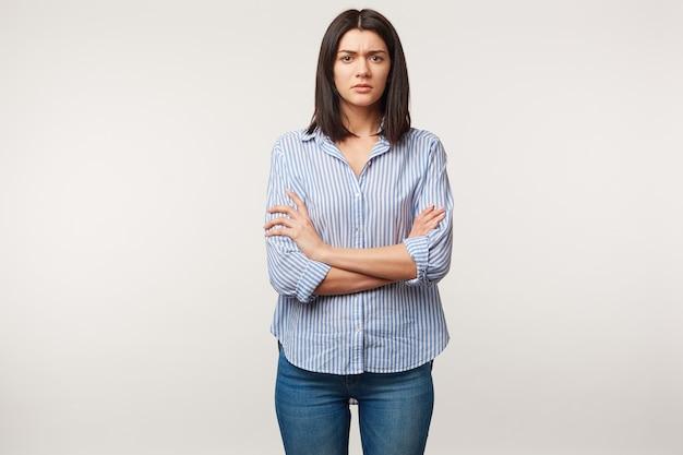 Foto interna de mulher morena, olha com desconfiança desconfiada desconfiada, tensa, escuta alguém com dúvida, estressante, em pé com os braços cruzados vestida de jeans e camisa listrada, sobre parede branca