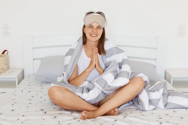 Foto interna de mulher sorridente com máscara de dormir e sendo enrolada em um cobertor, segurando as mãos em um gesto de súplica, mantendo as palmas das mãos juntas, olhando para a câmera com um sorriso encantador.