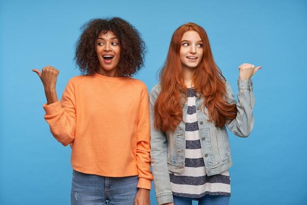 Foto interna de mulheres atraentes e agitadas apontando para lados diferentes, com batidas em relevo e rostos animados, em pé contra uma parede azul em roupas casuais