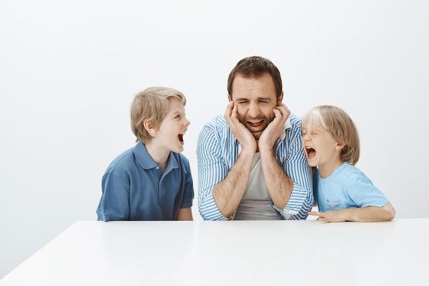 Foto interna de pai chorando chateado, sentado à mesa, gritando e apoiando as mãos no rosto, sentindo-se deprimido e infeliz enquanto os filhos faziam barulho e gritavam com ele