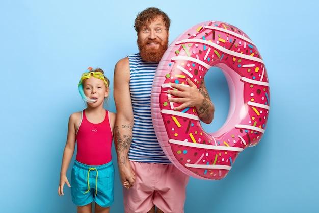 Foto interna de pai e filha ruivos encantados posando em trajes de piscina