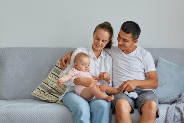 Foto interna de sorrindo, esposa e marido, vestindo roupas casuais, sentado no sofá com a encantadora filha infantil na sala de luz, passando um tempo feliz juntos.