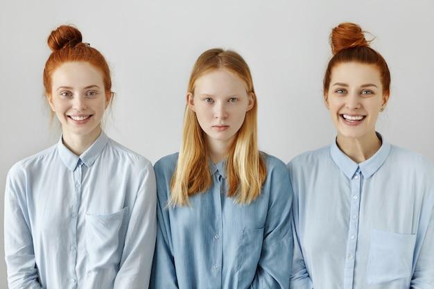 Foto interna de três mulheres brancas em camisetas semelhantes posando para a parede em branco do estúdio
