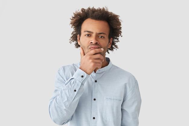 Foto interna de um afro-americano pensativo segurando o queixo e olhando com expressão séria, pensa no problema, veste uma camisa elegante, tem um penteado afro encaracolado
