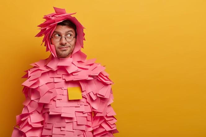 Foto interna de um anunciante ou gerente do sexo masculino coberta com notas adesivas, olha de lado enquanto observa algo interessante, posa contra uma parede amarela, espaço livre para seu conteúdo de publicidade