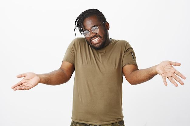 Foto interna de um cara bonito e descuidado com óculos posando contra a parede branca