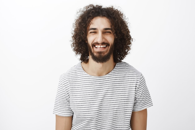 Foto interna de um cara brincalhão, bonito e amigável em uma camisa listrada da moda, apertando os olhos e rindo alto, ouvindo algo engraçado e curtindo um ótimo dia ensolarado de primavera
