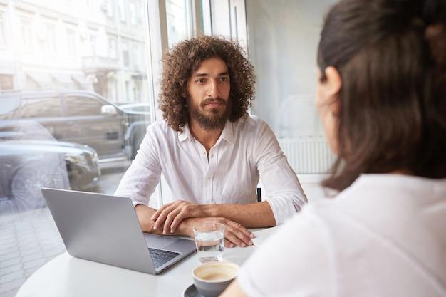 Foto interna de um cara cacheado bonito com barba sentado em um café com um parceiro de negócios, tendo um laptop e um copo de água na mesa, olhando atentamente para a pessoa ao lado dele