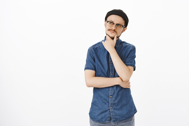 Foto interna de um cara caucasiano adulto atraente pensativo com gorro preto e óculos esfregando o bigode no queixo, olhando para o canto superior esquerdo, pensando concentrado, tomando decisões ou fazendo escolhas em mente