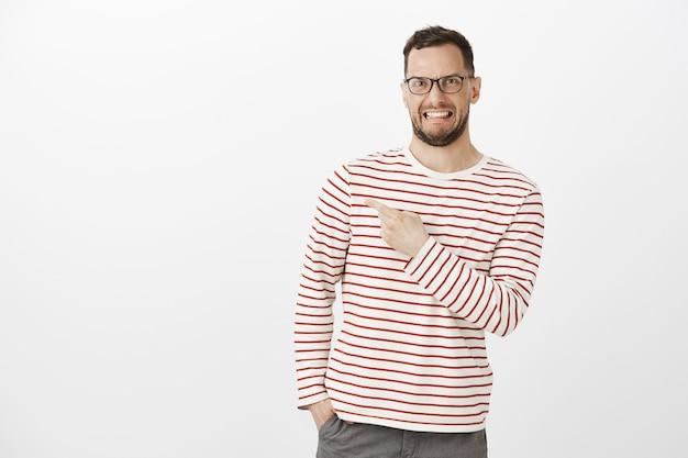 Foto interna de um cara engraçado enojado e descontente de óculos