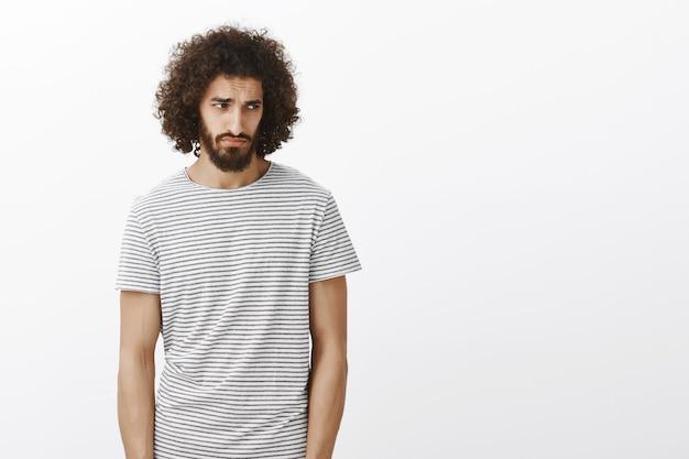 Foto interna de um cara hispânico bonito e sombrio em uma camiseta listrada, olhando por baixo da testa com uma expressão de ciúme miserável